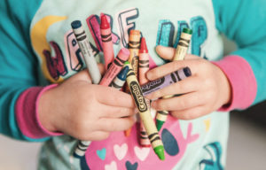 Adopted child holding crayons